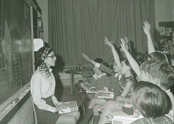 Elementary students learning from a teacher in the 1960s