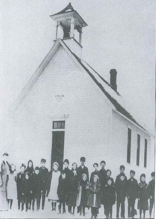 South School - White School house with bell tower and glass windows. School Children standing out front